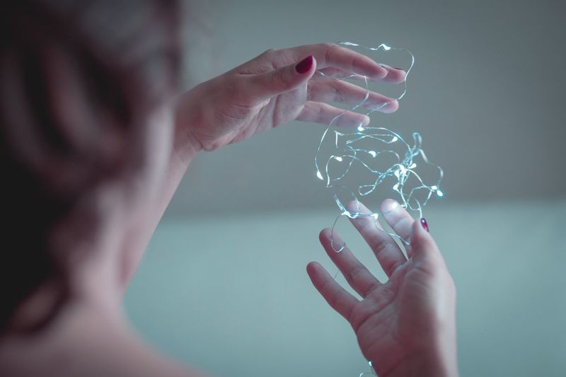 Close-Up Of Woman Holding Illuminated String Light