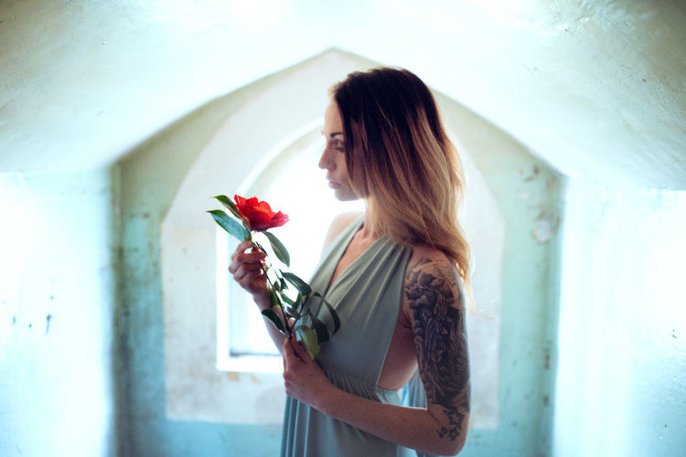 Woman holding rose while standing against white wall