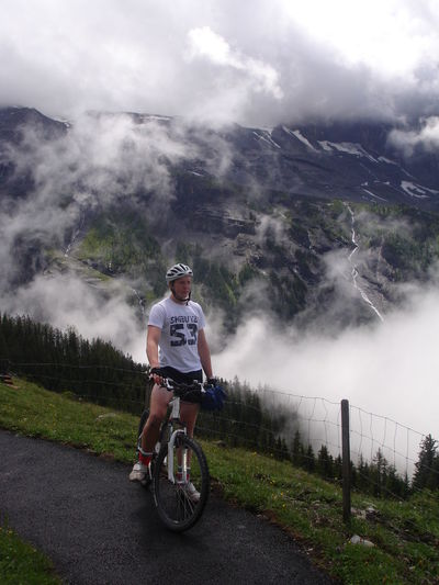 Full length of young man with mountain bike standing against cloudy sky