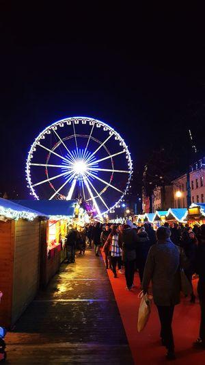 People at illuminated amusement park against sky at night