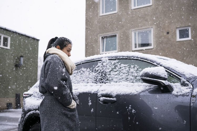 Woman standing on snow covered car against building during winter