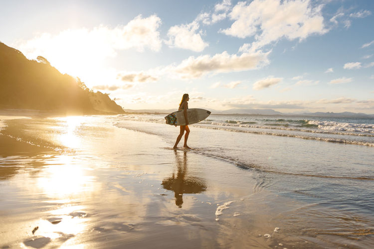 Byron Bay, Australia Water One Person Sky Sea Beach Leisure Activity Beauty In Nature Lifestyles Full Length Standing Cloud - Sky Real People Scenics - Nature Sunset Sunlight Outdoors Summer Travel Destinations Travel Golden Hour Women Surf Surfing Australia Byron Bay A New Perspective On Life Capture Tomorrow 2018 In One Photograph