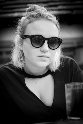 Portrait of young woman wearing sunglasses while sitting at table