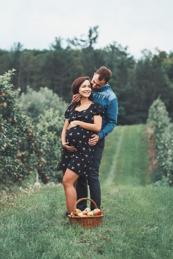 Full length of pregnant couple embracing by apples in basket on grass