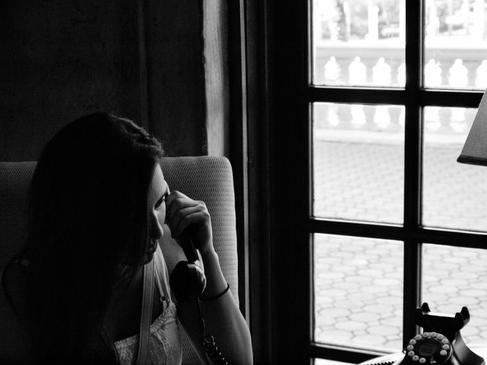 Woman talking on phone while sitting by window