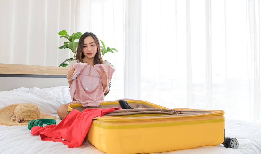 Young woman sitting on bed at home