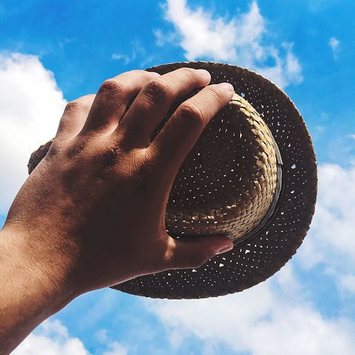 Cropped hand holding straw hat against sky