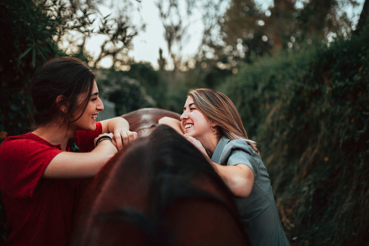 Smiling women with horse standing outdoors