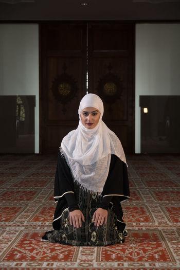 Woman in burka praying while kneeling on carpet
