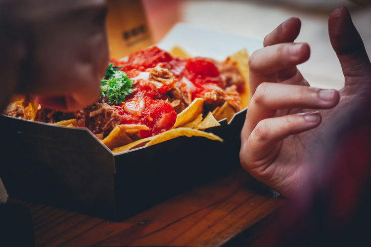Cropped Hand Of Person Eating Food On Table