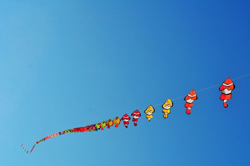 Low angle view of balloons flying against clear blue sky