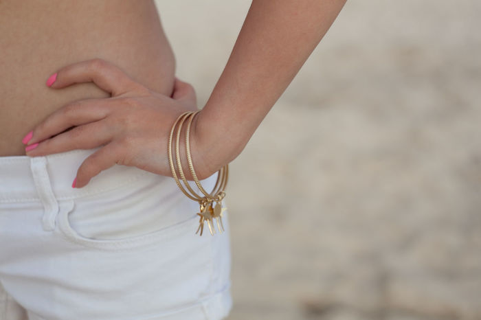 Beach Fashion: Charms Close Up Hand On Hip Shorts Midsection Pink Nails Tropical Gold Bracelet Golden Bracelet Charm Jewelry Slim City City Life Fashion Honolulu, Hawaii Individuality Sunny Accessories Apparel Beachwear Clothing Ethnic Islandstyle Multi Cultural Street Fashion Streetphotography Style Urban Young Adult