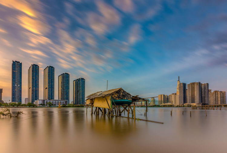 Panoramic view of sea and buildings against sky during sunset