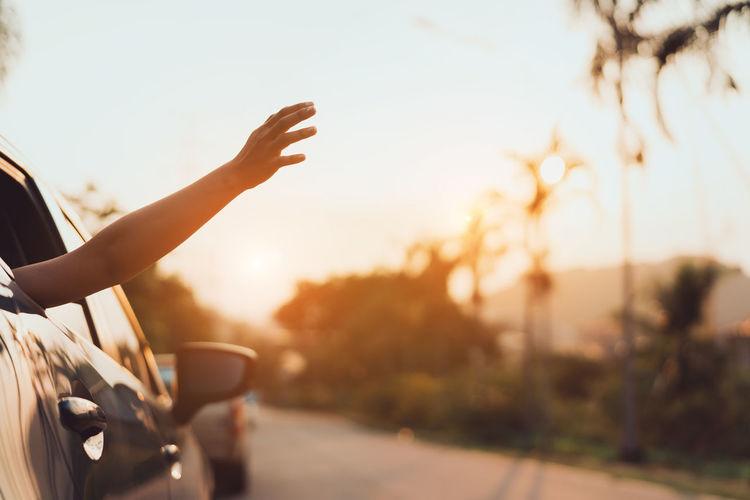 Cropped hand of woman peeking from car window