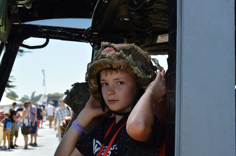 Portrait of boy wearing army helmet in vehicle