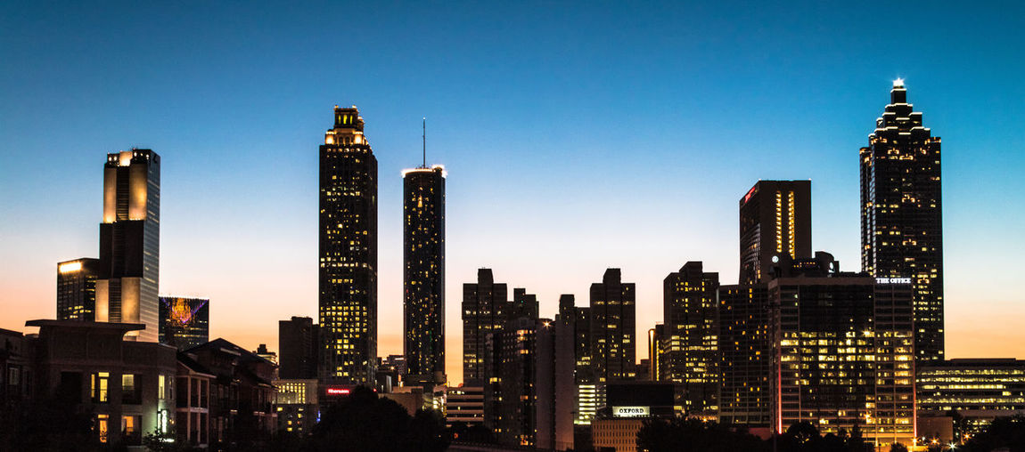Panoramic shot of illuminated buildings against clear sky