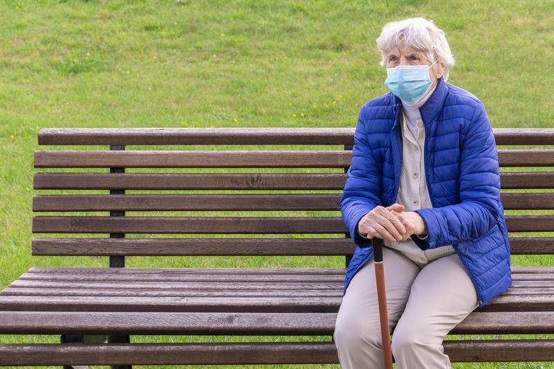 Senior woman wearing mask sitting outdoors