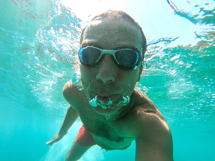 Underwater photo of a young active man swimming in turquoise sea water Swimming Leisure Activity Water Man Males  Sea Eyewear UnderSea Swimming Underwater Ocean Sea Water Blue Transparent Air Bubbles Snorkeling Fun Healthy Lifestyle Summer Vacation Tropical Tropical Paradise Thailand Maldives Phi Phi Island Underwater Selfie