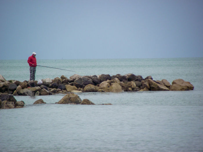Side View Of Man On Rock Fishing In Sea Against Clear Sky