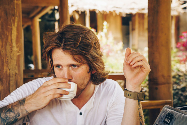 Young man drinking coffee in restaurant
