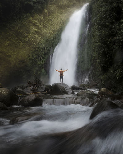 Rear view of man with arms outstretched against waterfall in forest
