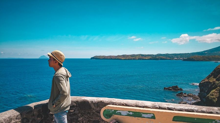 Man Standing At Observation Point By Sea Against Blue Sky