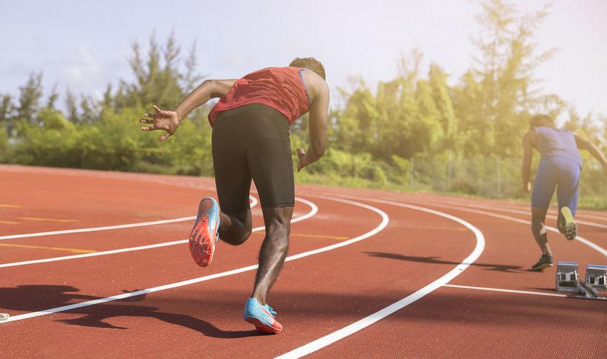 Rear view of men running on track