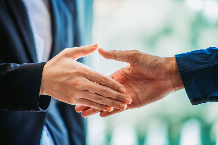 Midsection of business colleagues shaking hands at office