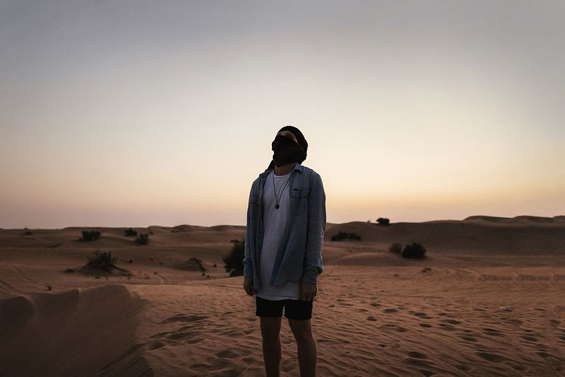 Rear view of man standing in desert against clear sky