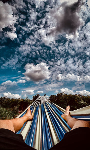 Low section of woman relaxing on hammock against sky