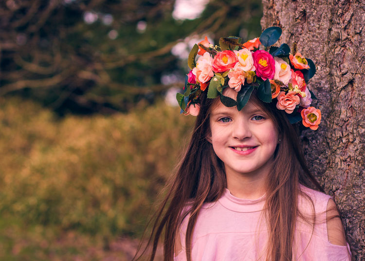 Child Childhood Flower Flower Head Flowering Plant Front View Girls Hairstyle Happiness Headshot Laurel Wreath Lifestyles Long Hair Looking At Camera Nature One Person Outdoors Plant Portrait Real People Smiling Wearing Flowers Women