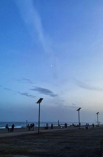 People on beach against sky at dusk