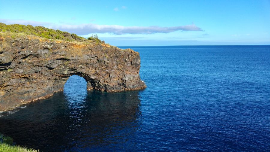 Rock formation at faial island by sea against sky