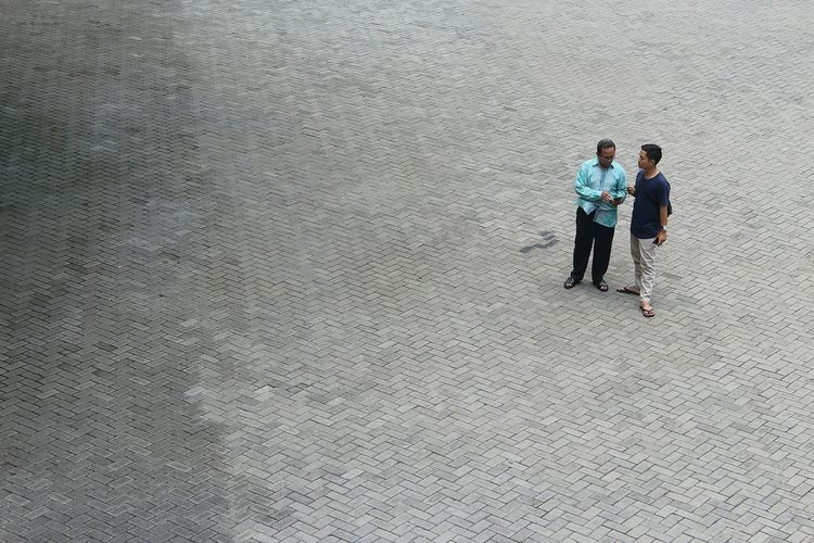 High Angle View Of People Talking While Standing On City Street