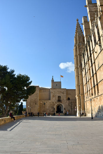 view of Royal Palace and cathedral in Palma di Maiorca Architecture Built Structure Building Exterior The Past Incidental People Religion Travel Destinations Outdoors Royal Palace Cathedral Palma De Mallorca Highlights Building Place Of Worship Belief Travel City History Footpath Sky