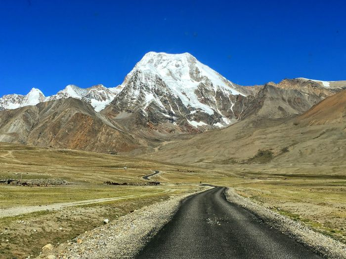 Road leading towards snowcapped mountain against clear blue sky