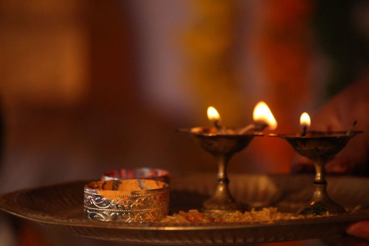 Close-up of illuminated diyas in plate on table