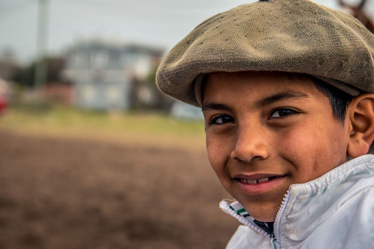 Close-up portrait of smiling boy wearing flat cap
