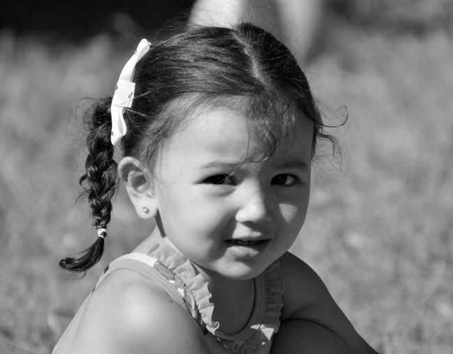 Close-up portrait of girl sitting on field