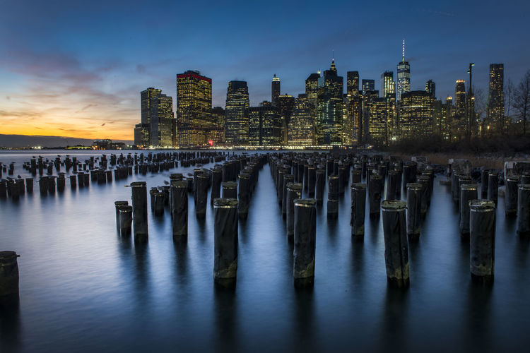 Wooden posts in sea against sky at dusk. skyline in background. manhattan at dusk.