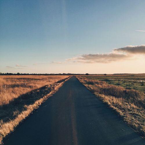 Single lane road on grassy field against sky