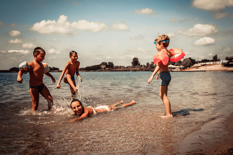 Playful kids and their mother having fun on the beach in summer.