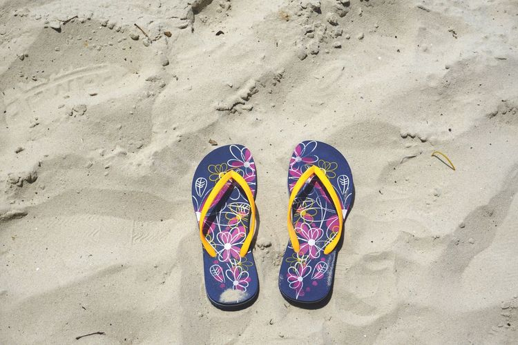 High Angle View Of Flip-Flops At Sandy Beach On Sunny Day