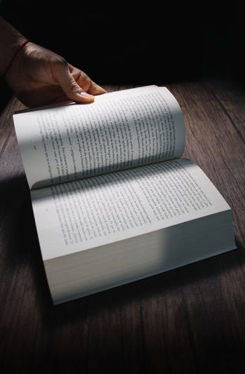 Close-up of hand holding book on table