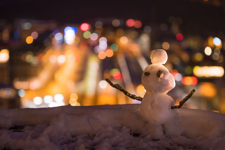 Close-up of figurine sculpture on snow against illuminated background at night