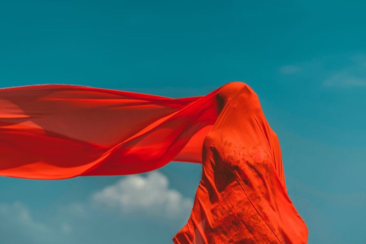 Woman covered with red fabric while standing against sky