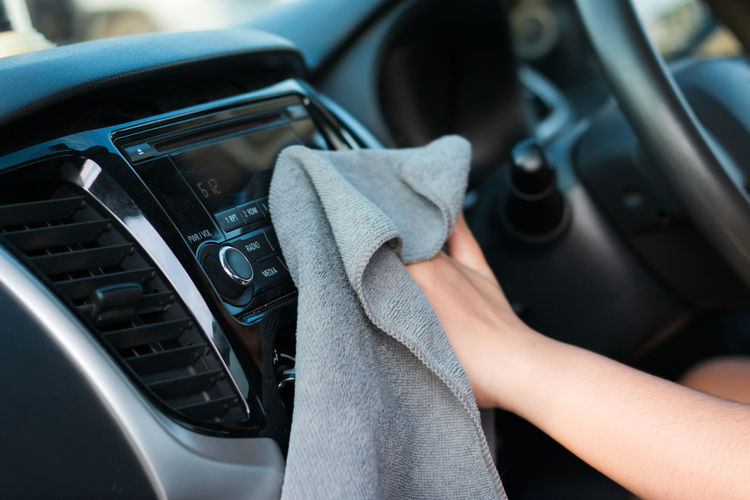 Midsection Of Woman Wiping Car With Fabric While Sitting In Car