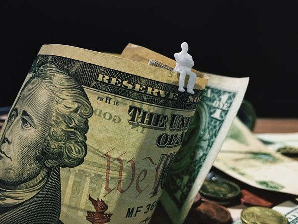man figurine sitting on dollar banknotes. Paper Currency Finance Male Likeness Currency Human Representation Wealth Politics Gambling Government Indoors  No People Close-up Passive Income Stock Market Investment Risk Management Financial Planning High Risk High Return Savings Money Game Money