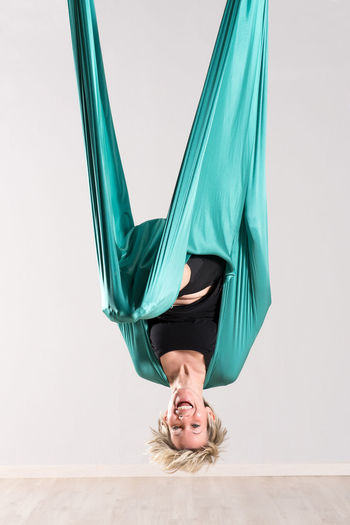 Laughing upside down woman doing aerial yoga Lifestyles Upside Down Real People Leisure Activity Emotion Fitness Laughing Exercise Supple Workout Aerial Yoga Adult Hanging Tarp Yoga Training Upside
