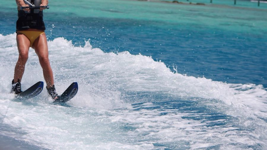 Low section of woman wakeboarding in sea